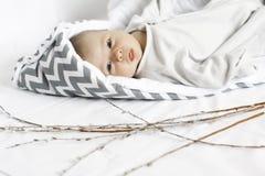 Petit enfant sur le fond blanc enfant dans l'enveloppe blanche et grise Photographie stock