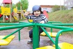 Petit enfant sur le terrain de jeu dehors Image libre de droits