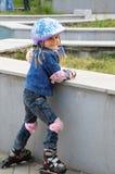 petit enfant sur les patins intégrés avec le casque photo stock