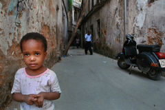 Petit enfant tenant dans une cour une vieille maison délabrée Photographie stock libre de droits