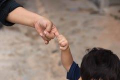 Petit enfant tenant son doigt du ` s de mère tout en marchant dehors Images libres de droits
