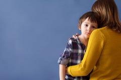 Petit enfant triste, garçon, étreignant sa mère à la maison image stock
