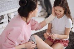 Petit enfant utile s'inquiétant de la mère à la maison Photo stock