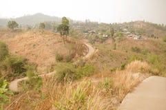 Petit enroulement de route bétonnée sur les collines sèches minuscules menant à un village tribal dans le nord de la Thaïlande pe photographie stock libre de droits