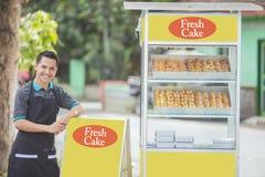 Petit entrepreneur et sa stalle de nourriture images stock
