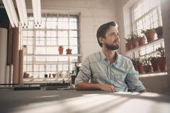 Petit entrepreneur regardant loin thoughfully dans son studio photos libres de droits