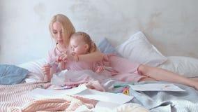 Petit feutre-stylo blond avec du charme de peinture de fille avec sa belle maman se trouvant sur le lit Dans des robes roses clips vidéos