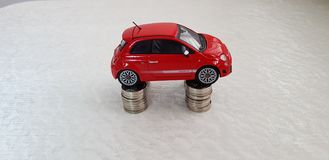 Petit Fiat rouge 500 supports de jouet sur quatre piles de pièces de monnaie israéliennes d'un shekel images libres de droits