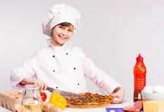 Petit fille-cuisinier de sourire avec la grande pizza dans des mains Image stock