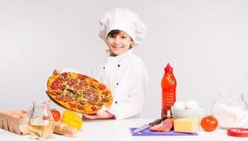 Petit fille-cuisinier de sourire avec la grande pizza dans des mains Photographie stock