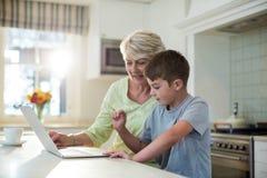 Petit-fils à l'aide de l'ordinateur portable avec la grand-mère Photographie stock