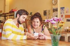 Petit-fils enseignant à sa grand-mère comment utiliser le téléphone portable Image libre de droits