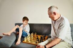 Petit-fils et grand-papa jouant des échecs Photographie stock libre de droits