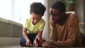 Petit fils mignon heureux jouant avec le puzzle se réunissant de papa noir banque de vidéos