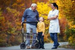 Petit-fils passant le temps en parc avec le grand-père supérieur handicapé Photos stock