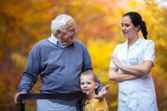 Petit-fils passant le temps en parc avec le grand-père supérieur handicapé Images libres de droits