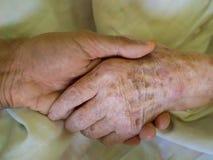 Petit-fils tenant la main de sa grand-mère dans l'hôpital image libre de droits