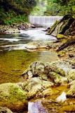 Petit fleuve avec la cascade à écriture ligne par ligne et les roches. Photographie stock