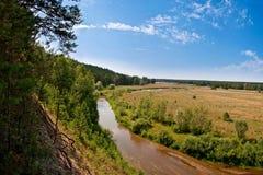 Petit fleuve en bois près de plaine Images stock
