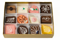 Petit fours. An assortment of petit fours in a gold box Royalty Free Stock Images