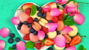 Petit Fours presentation of macarons with berries and rose petal Royalty Free Stock Photos