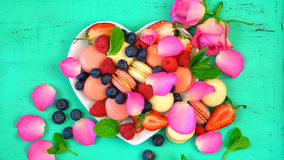 Petit Fours presentation of macarons with berries and rose petal Royalty Free Stock Photography
