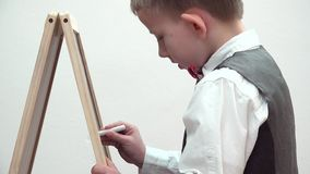 Petit foyer d'écriture d'écolier au panneau de craie, enfant soigneux à son activité clips vidéos