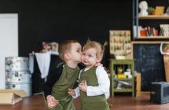 Petit frère embrassant sa jolie soeur dans une classe créative Photos stock