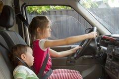 Petit frère et soeur de sourire conduisant en voiture de jouet Photos stock
