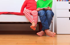 Petit frère et soeur regardant le téléphone portable, foyer sur des pieds Image stock
