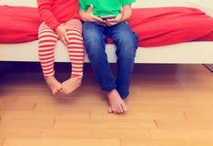 Petit frère et soeur regardant le téléphone portable, foyer sur des pieds Photographie stock libre de droits