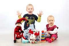 Petit frère et soeur s'asseyant avec des cadeaux et des jouets de Noël Photographie stock