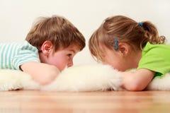Petit frère et soeur se trouvant sur l'étage Images stock