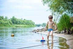 petit frère jouant avec les bateaux de papier par une rivière le jour chaud et ensoleillé d'été Photographie stock