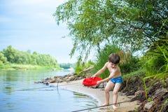 petit frère jouant avec les bateaux de papier par une rivière le jour chaud et ensoleillé d'été Images stock