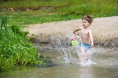 petit frère jouant avec les bateaux de papier par une rivière le jour chaud et ensoleillé d'été Image libre de droits