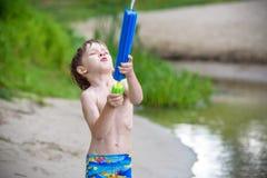 petit frère jouant avec les bateaux de papier par une rivière le jour chaud et ensoleillé d'été Photo libre de droits