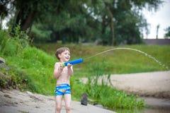 petit frère jouant avec les bateaux de papier par une rivière le jour chaud et ensoleillé d'été Image stock