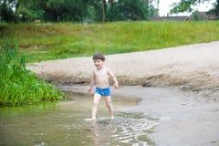 petit frère jouant avec les bateaux de papier par une rivière le jour chaud et ensoleillé d'été Photos stock