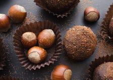 Petit fyra sötsaker och hasselnötter för choklad Arkivbilder