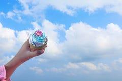 Petit gâteau à disposition sur le fond de ciel bleu Images stock