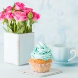 Petit gâteau avec de la crème bleue douce et les roses roses dans le rétro vase chic minable sur le fond en pastel bleu Photos stock