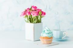 Petit gâteau avec de la crème bleue douce et les roses roses dans le rétro vase chic minable sur le fond en pastel bleu Images libres de droits