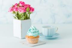 Petit gâteau avec de la crème bleue douce et les roses roses dans le rétro vase chic minable sur le fond en pastel bleu Photo stock