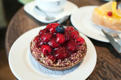 Petit gâteau avec des framboises dans un café photos stock