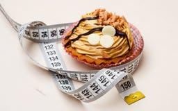 Petit gâteau avec la bande de mesure sur la table Image stock