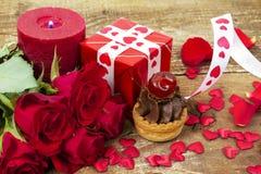Petit gâteau avec la cerise devant le bouquet des roses rouges Photo stock