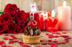 Petit gâteau avec la cerise devant le bouquet des roses rouges Photo libre de droits