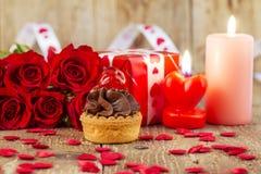 Petit gâteau avec la cerise devant le bouquet des roses rouges et des cadles Photo stock