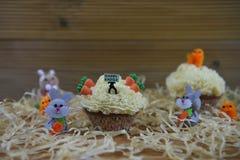 Petit gâteau avec la figurine miniature de personne jugeant un panneau de signe pour Joyeuses Pâques entouré par des décorations Photo stock